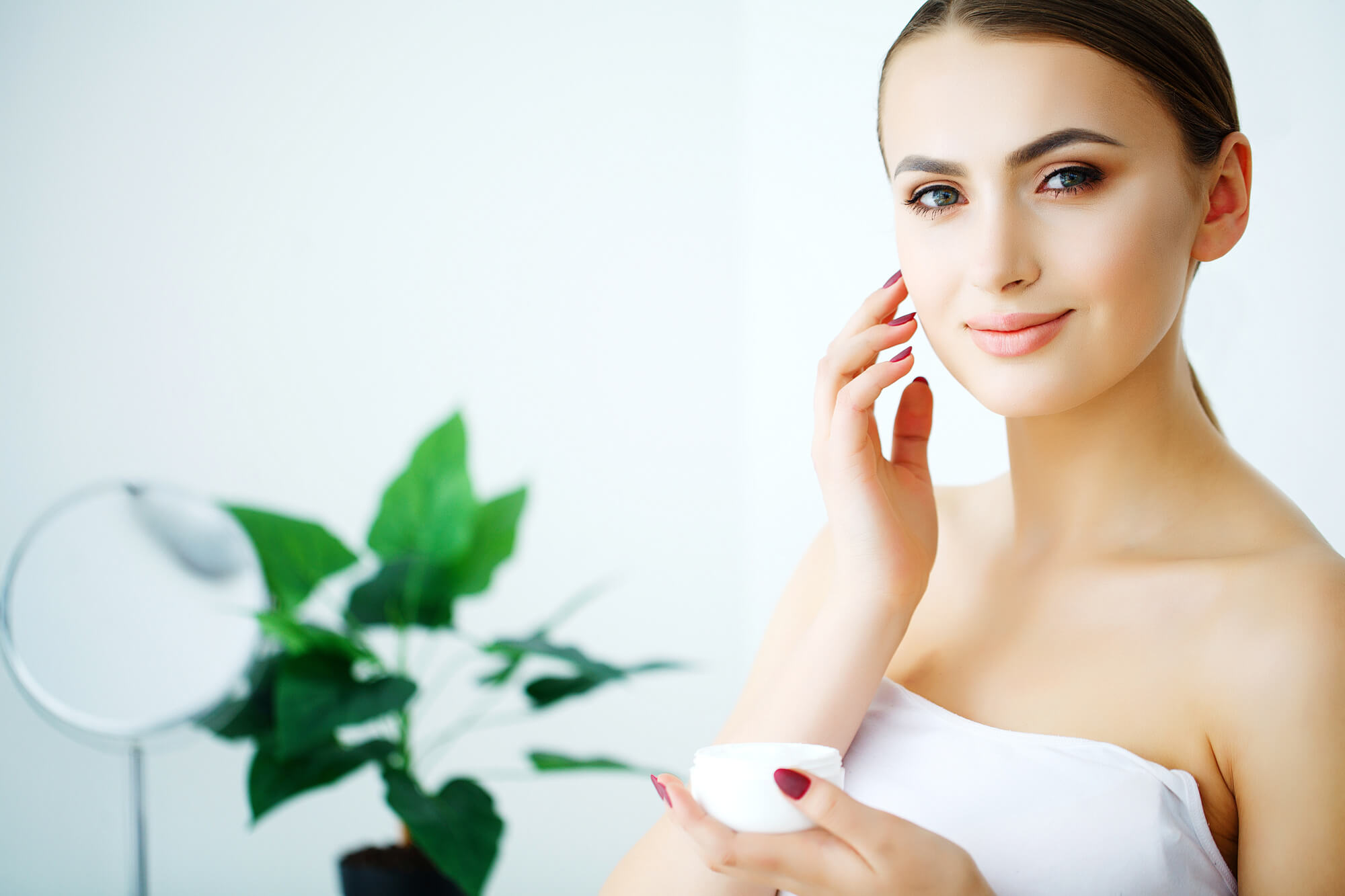 Woman smiling with skin cream jar and plant in background